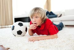 Animated boy watching football match lying on the floor - stock photo