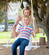 Stock Photo of Jolly mother pushing her daughter on a swing