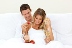Lovers drinking Champagne with strawberries - stock photo