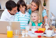 Blissful family using laptop during the breakfast - stock photo