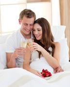 Cheerful couple drinking champagne with strawberries lying in bed - stock photo