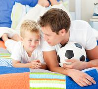 Attentive father and his son playing with a soccer ball - stock photo