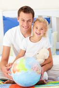 Attentive father and his daugther looking at a terrestrial globe - stock photo