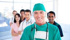 Assertive senior surgeon standing with his colleagues Stock Photos