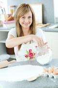 Portrait of a cheerful woman preparing a cake in the kitchen - stock photo