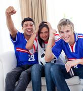 Adolescents watching a football match at home Stock Photos