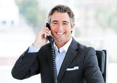 Self-assured mature businessman talking on phone - stock photo