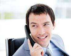 Assertive young businessman talking on phone Stock Photos