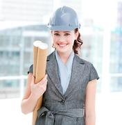 Portrait of a self-assured female architect holding blueprints Stock Photos