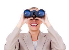 Joyful businesswoman predicting future success through binoculars - stock photo