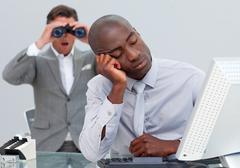 Asleep businessman annoyed by a man looking through binoculars Stock Photos
