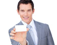 Self-assured businessman showing a white card Stock Photos