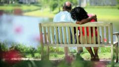 Senior ethnic couple sitting bench enjoying lake view  - stock footage
