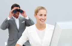 Ambitious manager holding binoculars looking at his colleague's computer Stock Photos