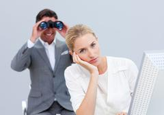 Blond businesswoman annoyed by a man looking through binoculars - stock photo