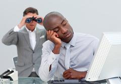 Unhappy businessman getting bored and his manager looking through binoculars Stock Photos