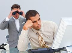 Young businessman getting bored and his manager looking through binoculars - stock photo