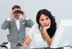 Brunette businesswoman getting bored and her manager looking through binoculars Stock Photos