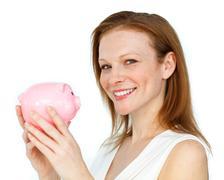 Self-assured businesswoman holding a piggybank - stock photo