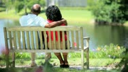 Loving ethnic couple planning future on bench lake view  Stock Footage
