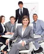 Assertive female executive sitting in front of her team Stock Photos