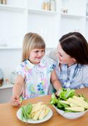 Attentive mother and her daughter eating vegetables - stock photo
