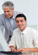 Confident businessman helping his colleague at a computer Stock Photos