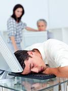 Tired businessman sleeping on his keyboard Stock Photos