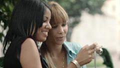 Two happy young women looking at pictures on snapshot camera Stock Footage