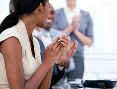 Happy business team applauding in a meeting - stock photo