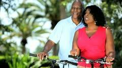 Senior ethnic couple enjoying park cycle track  Stock Footage