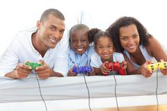 Animated family playing video game lying down on bed - stock photo