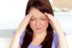 young woman with headache at home - stock photo