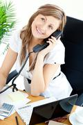 self-assured businesswoman talking on phone sitting at her desk - stock photo