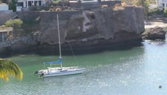 Sailboat in water, nature scene, cliff, rocks, palm tree, house Stock Footage