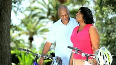 Mature diverse couple getting ready for cycling  Stock Footage