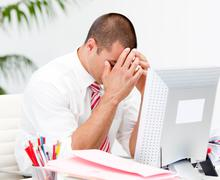 frustrated businessman working at a computer - stock photo
