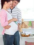 Smiling pregnant woman holding baby shoes while husband touching her belly Stock Photos