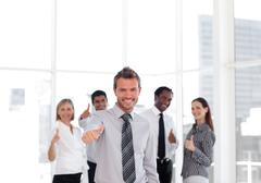 self-assured business manager standing at the camera with his team - stock photo