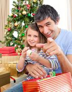 father and little girl playing with christmas presents - stock photo