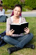 Stock Photo of bright female student reading a book sitting on the grass