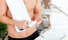 close-up of a young muscular man ready to shave in the bathroom - stock photo