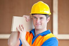 Young male worker carrying a wooden board Stock Photos