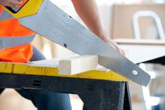 Close-up of a serious male worker sawing a wooden board Stock Photos