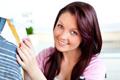 Stock Photo of smiling caucasian woman sewing in the kitchen