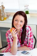 radiant caucasian woman holding an apple sitting in the kitchen - stock photo