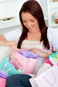 smiling caucasian woman opening her shopping bags on the sofa - stock photo
