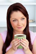 positive woman holding a cup of coffee at home - stock photo
