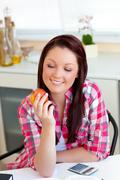 Stock Photo of smiling caucasian woman holding an apple sitting in the kitchen