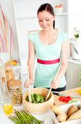 glowing young woman preparing salad at home - stock photo